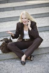 Junge Frau mit Handy, sititng auf Schritte