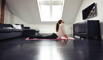 Young brunette exercising on floor at home