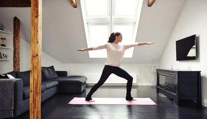 Attractive young woman doing yoga at home