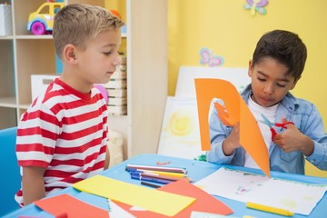 Cute little boys cutting paper shapes in classroom