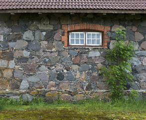 Wall from granite stones with a window and a tree, the old aspha