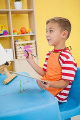 Cute little boy painting at table in classroom