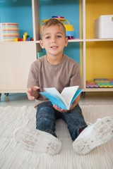 Cute little boy sitting on floor reading in classroom