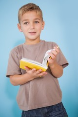 Cute little boy reading in classroom