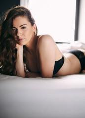 Pretty woman wearing black lingerie lying on bed