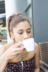 Beautiful latin woman drinking and enjoying a cup coffee.