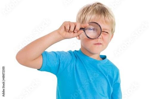 Ładny mały chłopiec patrząc przez szkło powiększające