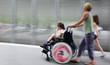 Leinwanddruck Bild - disabled child in a wheelchair on a city street