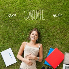 Graduate against pretty student lying on grass