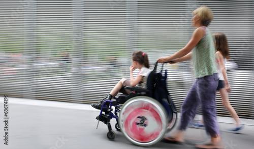Leinwanddruck Bild disabled child in a wheelchair on a city street