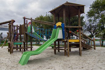 View of a urban wooden playground for kids with sand and slides.
