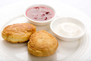 Fried buns on the plate with jam and sour cream