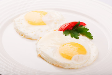 Fried eggs decorated with parsley and tomato