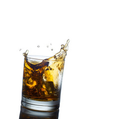 Scotch whiskey splashing out of glass. Isolated on white  backgr