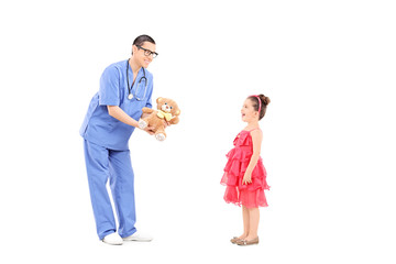 Doctor giving teddy bear to a surprised little girl