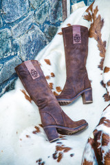 suede boots are on the skin near the fireplace
