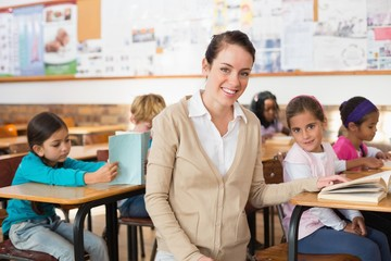 Pretty teacher smiling at camera with her class