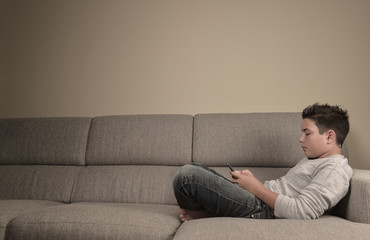Teenage boy with phone at home lying on a sofa