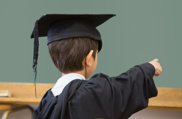 Cute pupil in graduation robe pointing in classroom