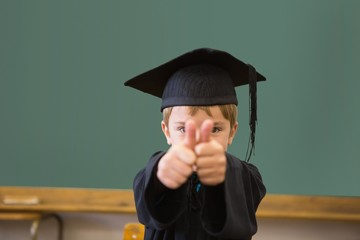Cute pupil in graduation robe smiling at camera in classroom