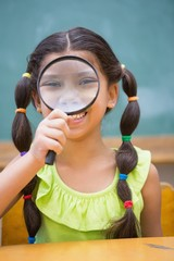 Cute pupil looking through magnifying glass in classroom