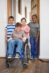 Disabled pupil with his friends in classroom