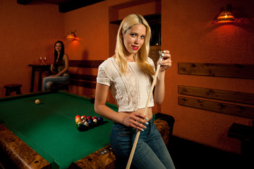 Beautiful young blonde woman playing billiard in a bar