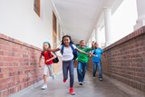 Cute pupils running and smiling at camera in hallway