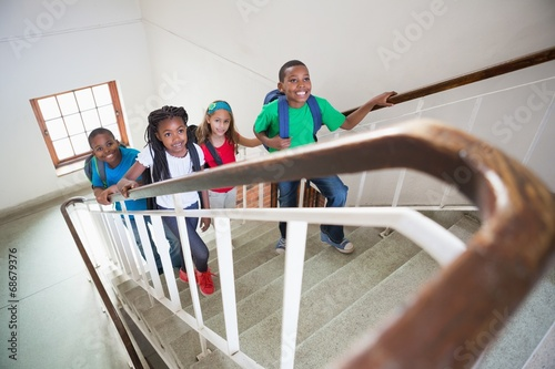 Cute pupils smiling and walking up stairs - 68679376