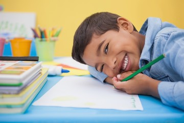 Cute little boy drawing at desk