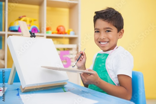 canvas print picture Cute little boy painting at table in classroom