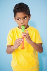 Cute little boy playing the recorder in classroom