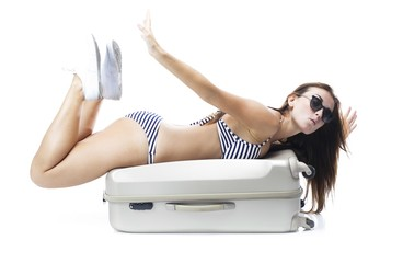 Tourist woman in bikini laying on suitcase