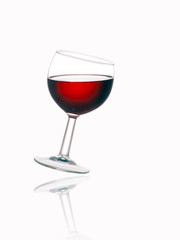 Glass of red wine, tilted, with reflection, white background.