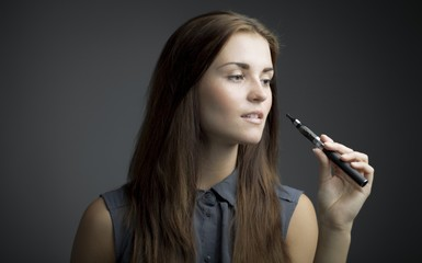 Elegant, beautiful woman smoking e-cigarette