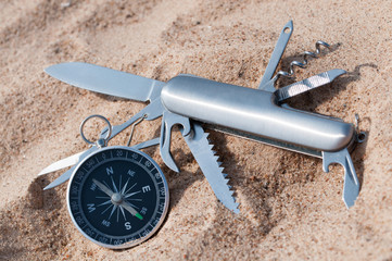 Compass and knife on the sea sand.