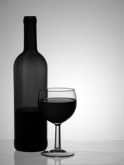 Red wine bottle and glass, monochrome black and white, backlit.