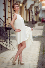 Perfect elegantly blonde woman in white dress on the street