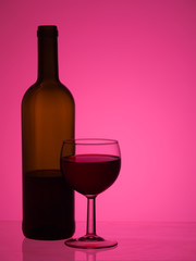 Bottle and glass of red wine over bright pink background.