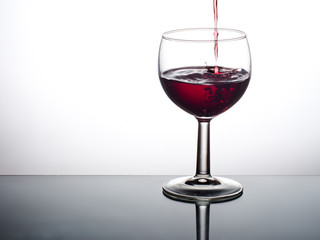 A nice drop of red wine - poured into glass.