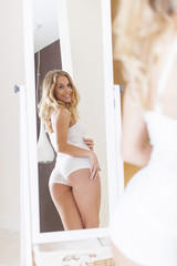 Blonde woman looking on buttocks in mirror