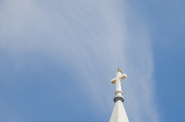 Church steeple, rooster on top with blue sky in background
