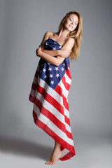Beautiful woman wrapped in American flag