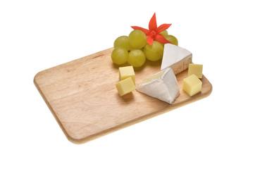 Kleines Holzbrett auf weiss mit Käse und Deko