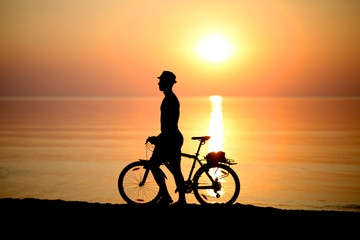Silhouette of a man with a becycle on beach at sunset