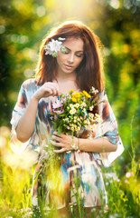 Young beautiful red hair woman holding a wild flowers bouquet