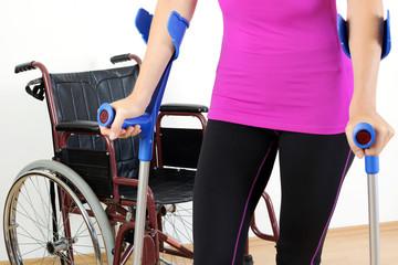 Frau mit Gehbehinderung geht auf Krücken