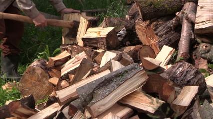 Peasant worker man chop wood nead firewood pile. Closeup