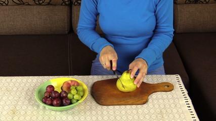 Young pregnant woman hands cut pear for fruit salad. Closeup