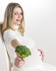 portrait of pregnant woman holding broccoli